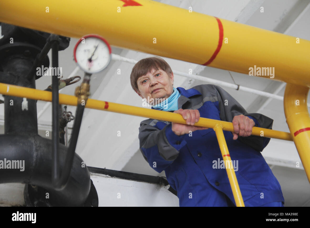The elderly woman in work overalls on manufacturing site is checking gauge - Stock Image