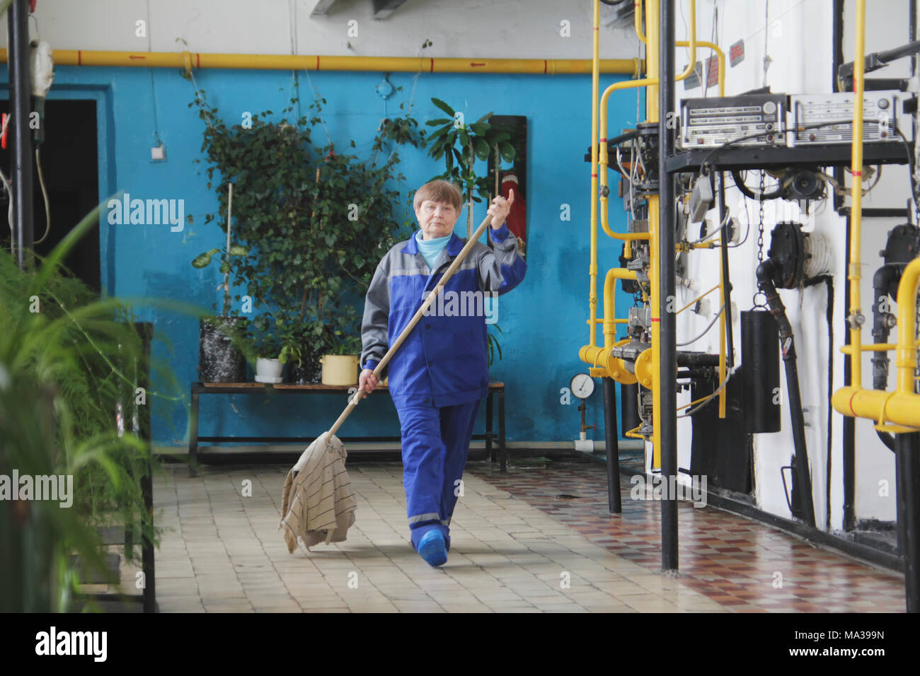 Old woman cleaner in workwear on manufacturing site - Stock Image