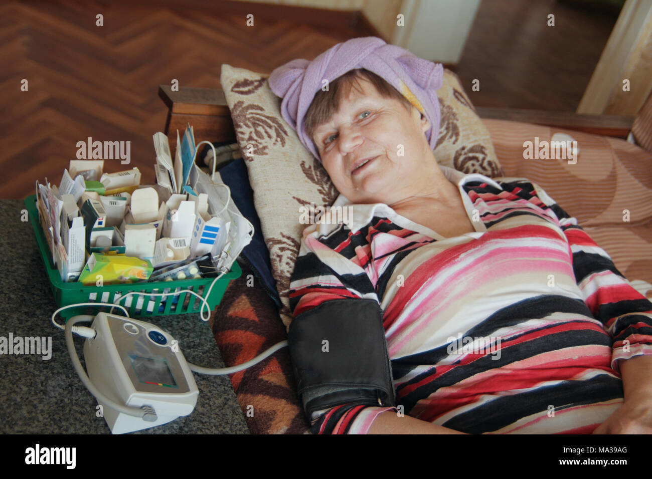 Sick senior woman lying at bed with tablets and device for measuring pressure - Stock Image