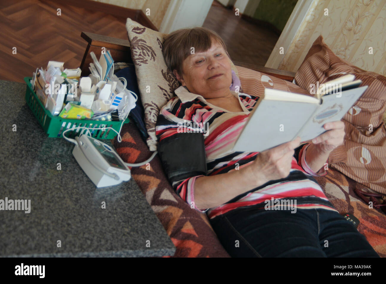 Sick senior woman reading at bed with tablets and device for measuring pressure - Stock Image