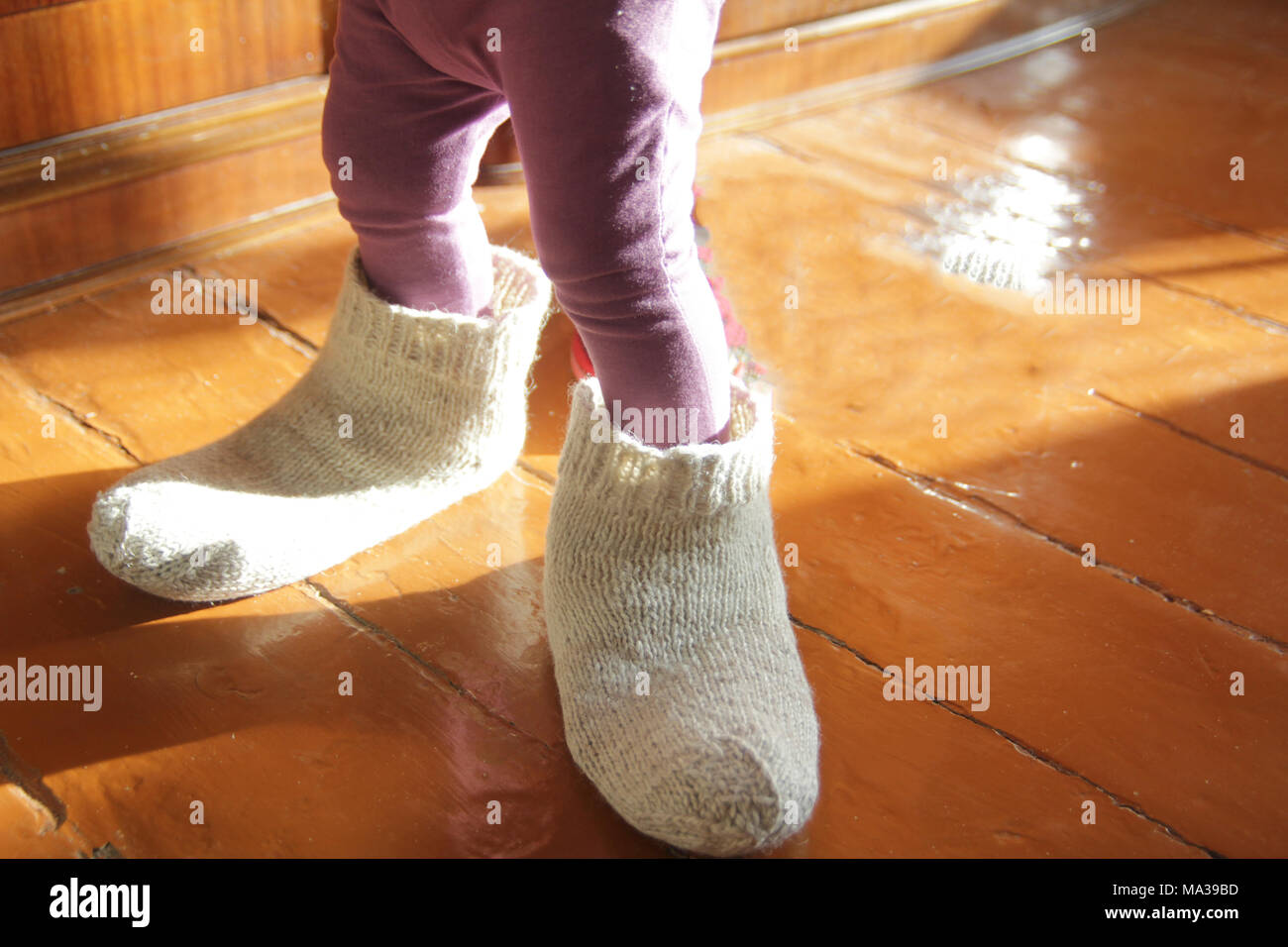 Little girl trying on dad's wool socks at home - Stock Image