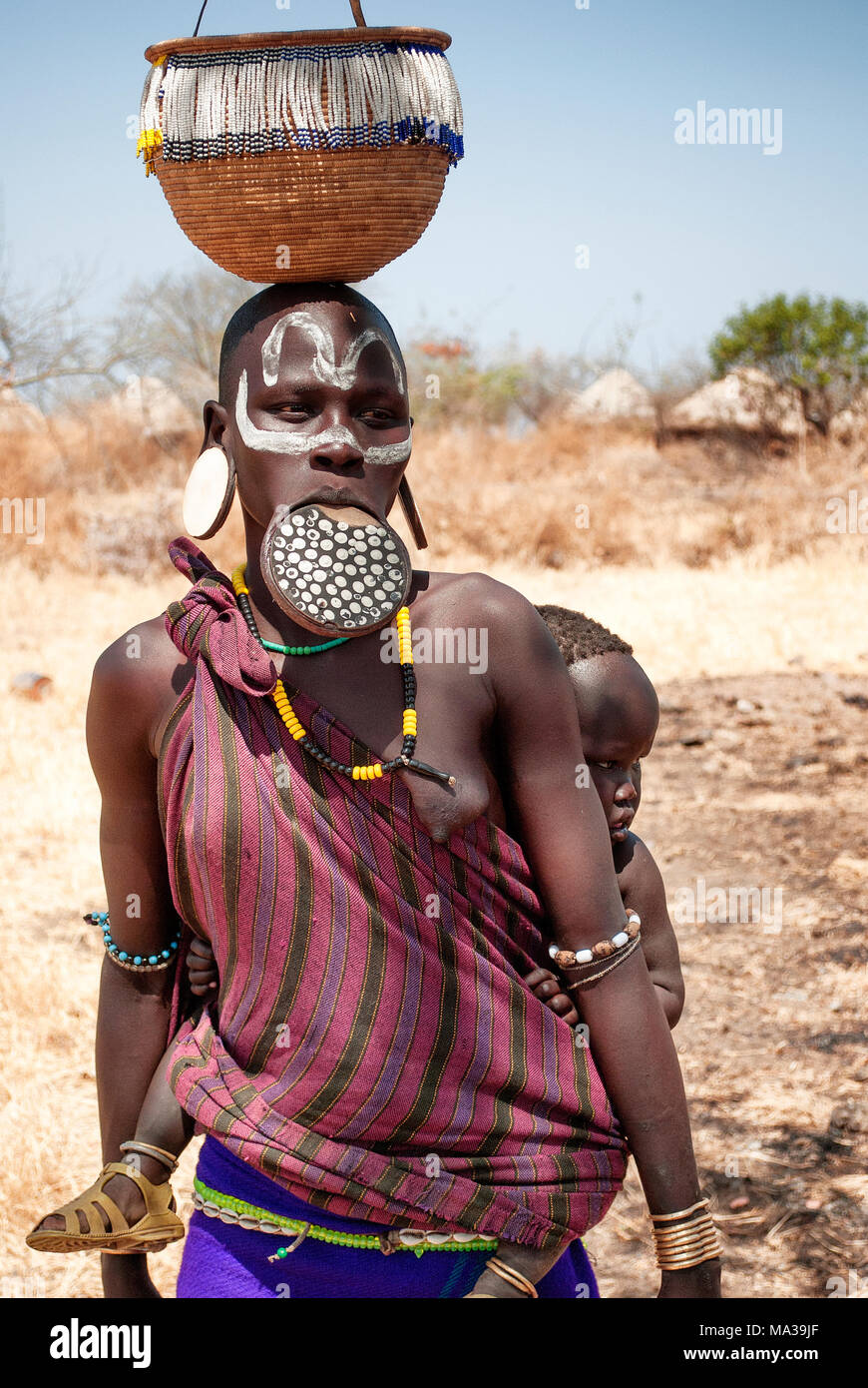 Mursi woman with labial plate and son on her back, ethnic minorities of the lower Omo valley - Ethiopia. © Antonio Ciufo - Stock Image