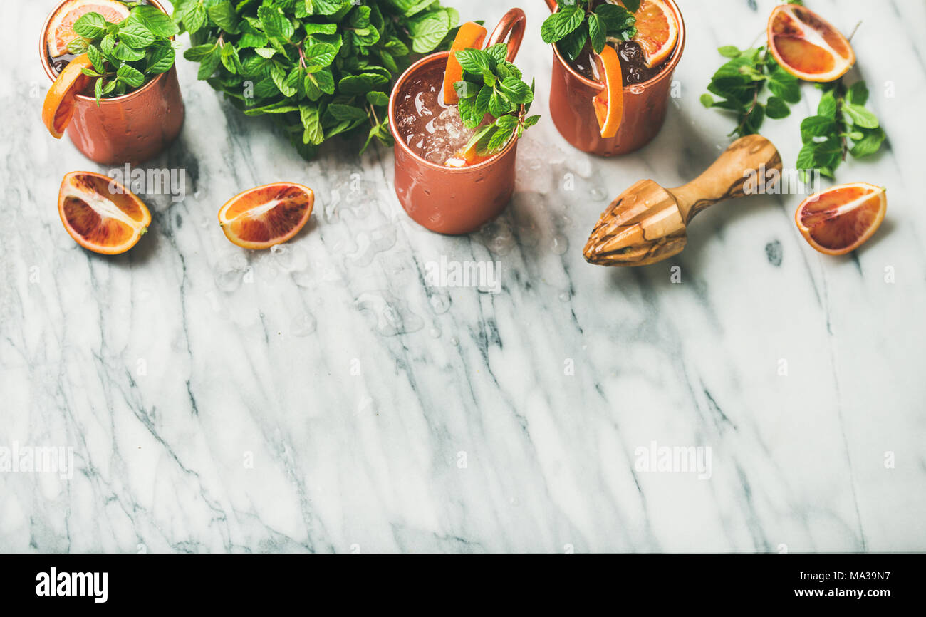 Blood orange Moscow mule alcohol cocktails over marble background - Stock Image