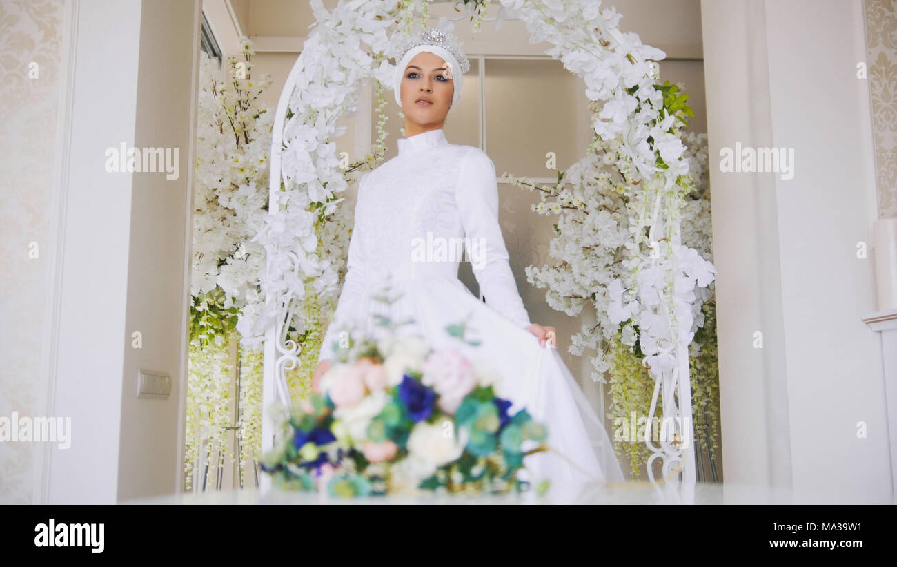 Beautiful muslim bride with make up in white wedding dress comes to ...