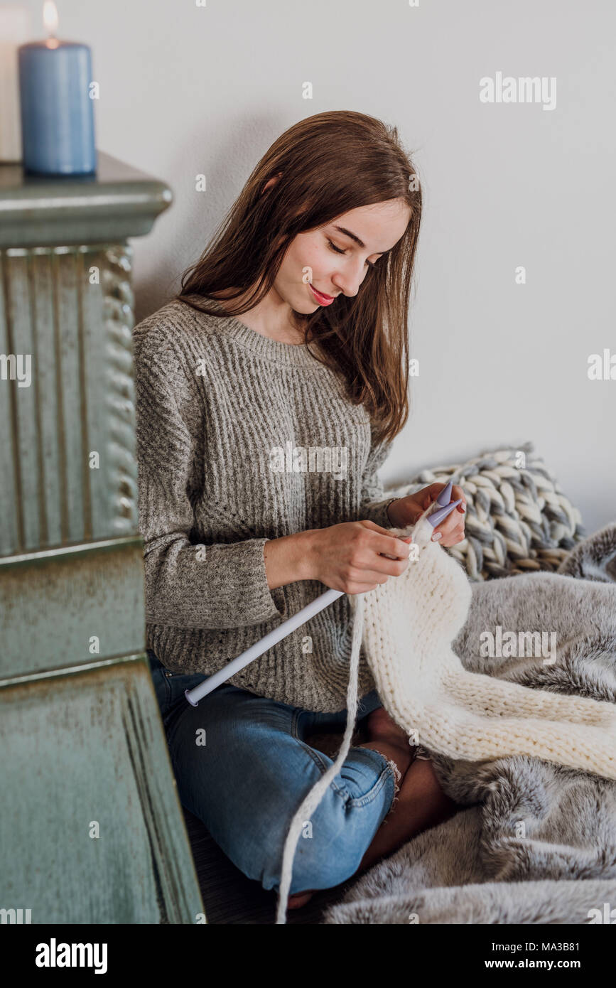 young woman sits next to a tiled stove and knits - Stock Image