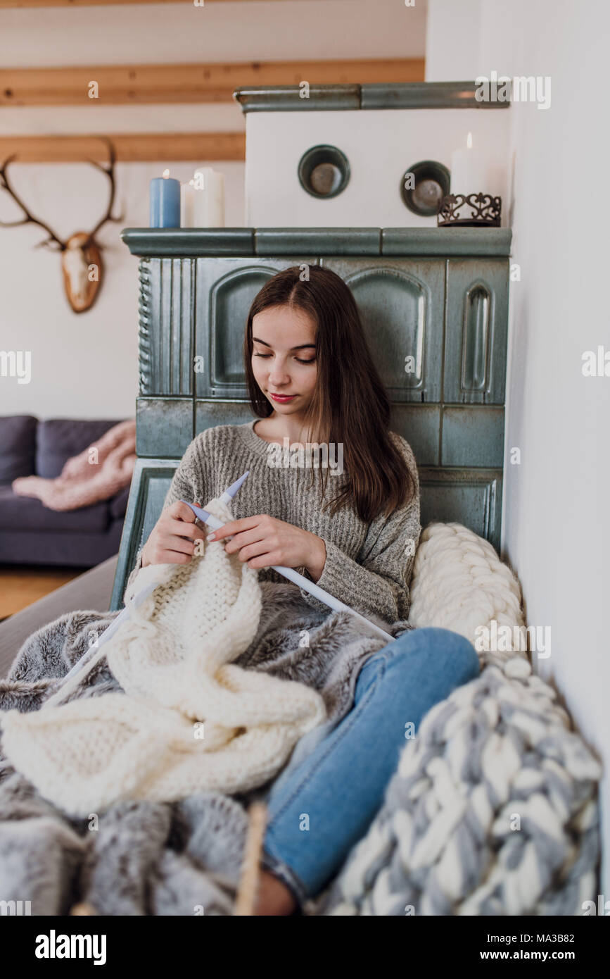 young woman sits next to a tiled stove and knits,detail, - Stock Image