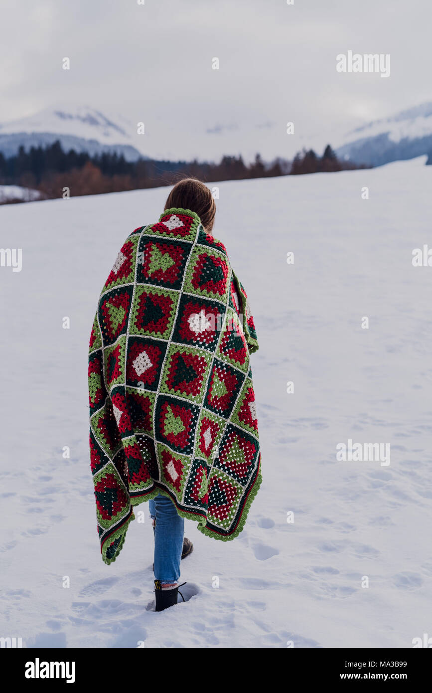 young woman wrapped in a blanket is standing in the snow, - Stock Image
