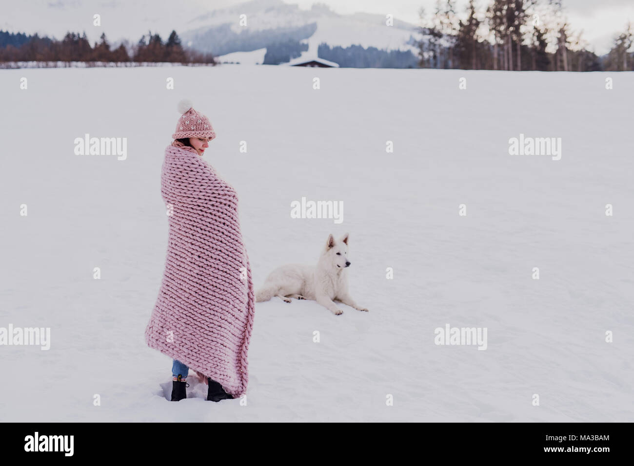 young woman stands wrapped in a pink blanket in a winter landscape,dog lies next to her in the snow, - Stock Image