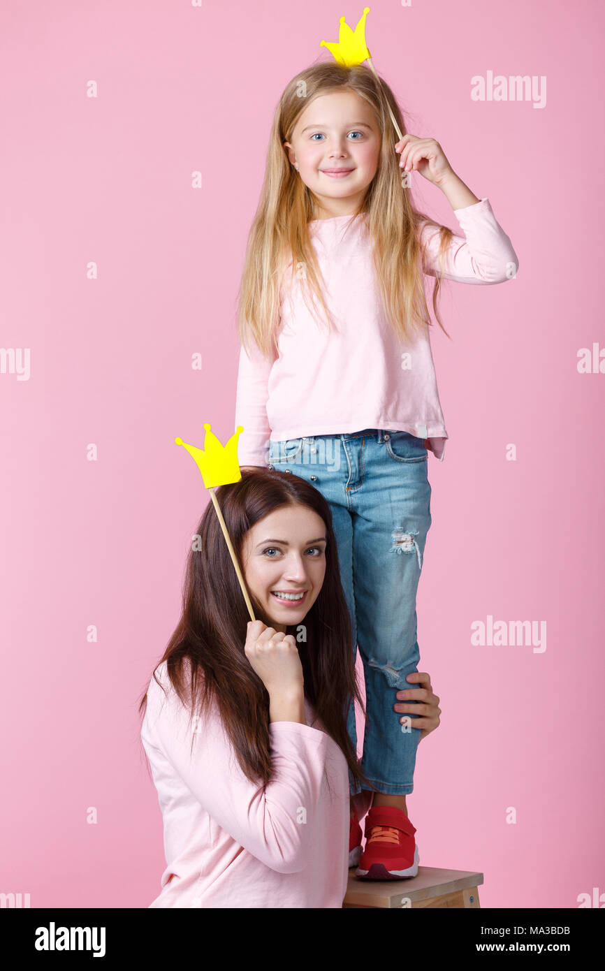 young mother and daughter having fun together and holding paper yellow crown on pink background - Stock Image
