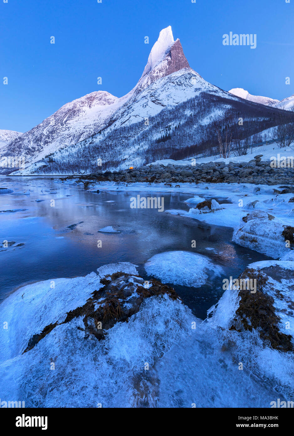 Twilight on frozen sea in  Tysfjord and over Norway's national mountain called Stetind,tysfjord Nordland county Norway Europe - Stock Image