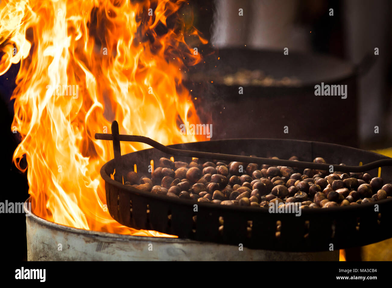 a suggestive snapshot of a cooking pan full of chestnuts roasting by the fire, Bolzano province, South Tyrol, Trentino Alto Adige, Italy - Stock Image
