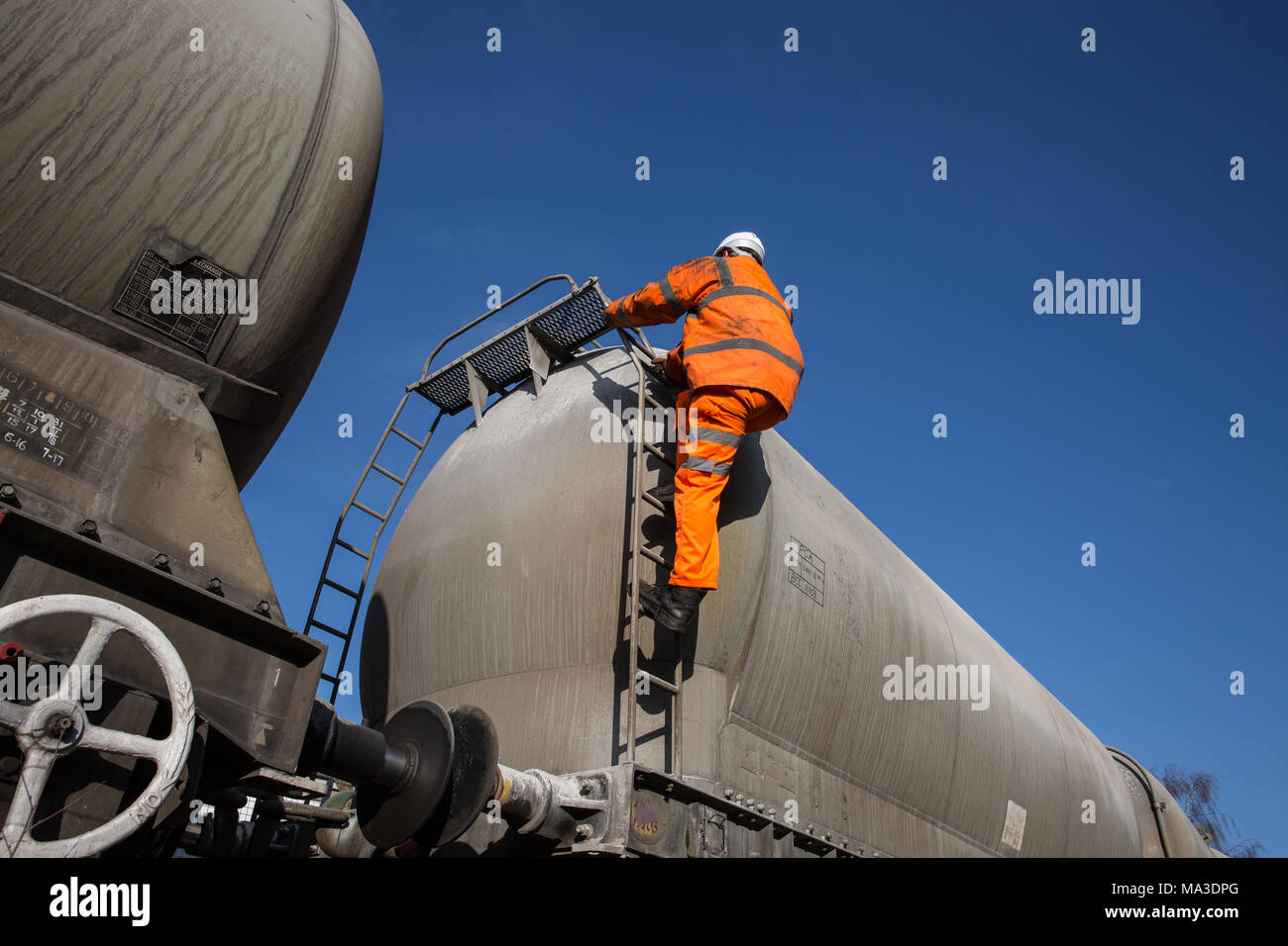 A railway maintenance worker wearing hi viz clothing climbing a ladder onto a rail tanker to inspect the upper deck whilst working at height. Stock Photo