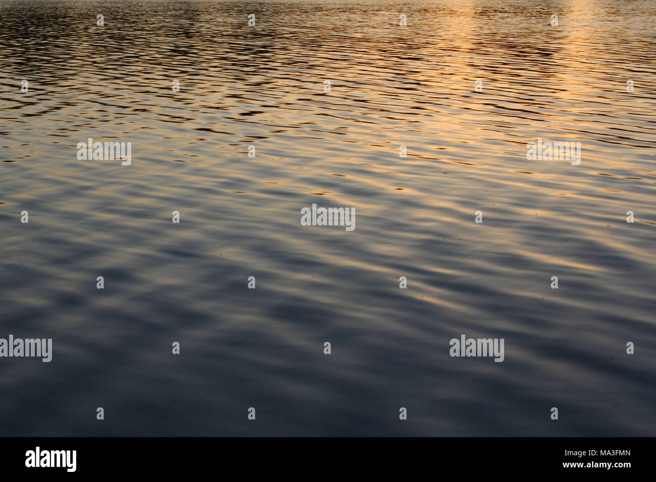 Gentle waves on reflecting water surface - Stock Image