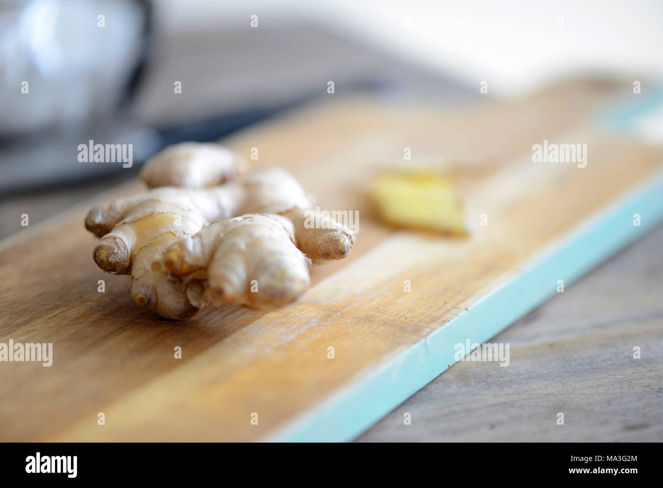 Ginger rhizome, piece, wooden board - Stock Image