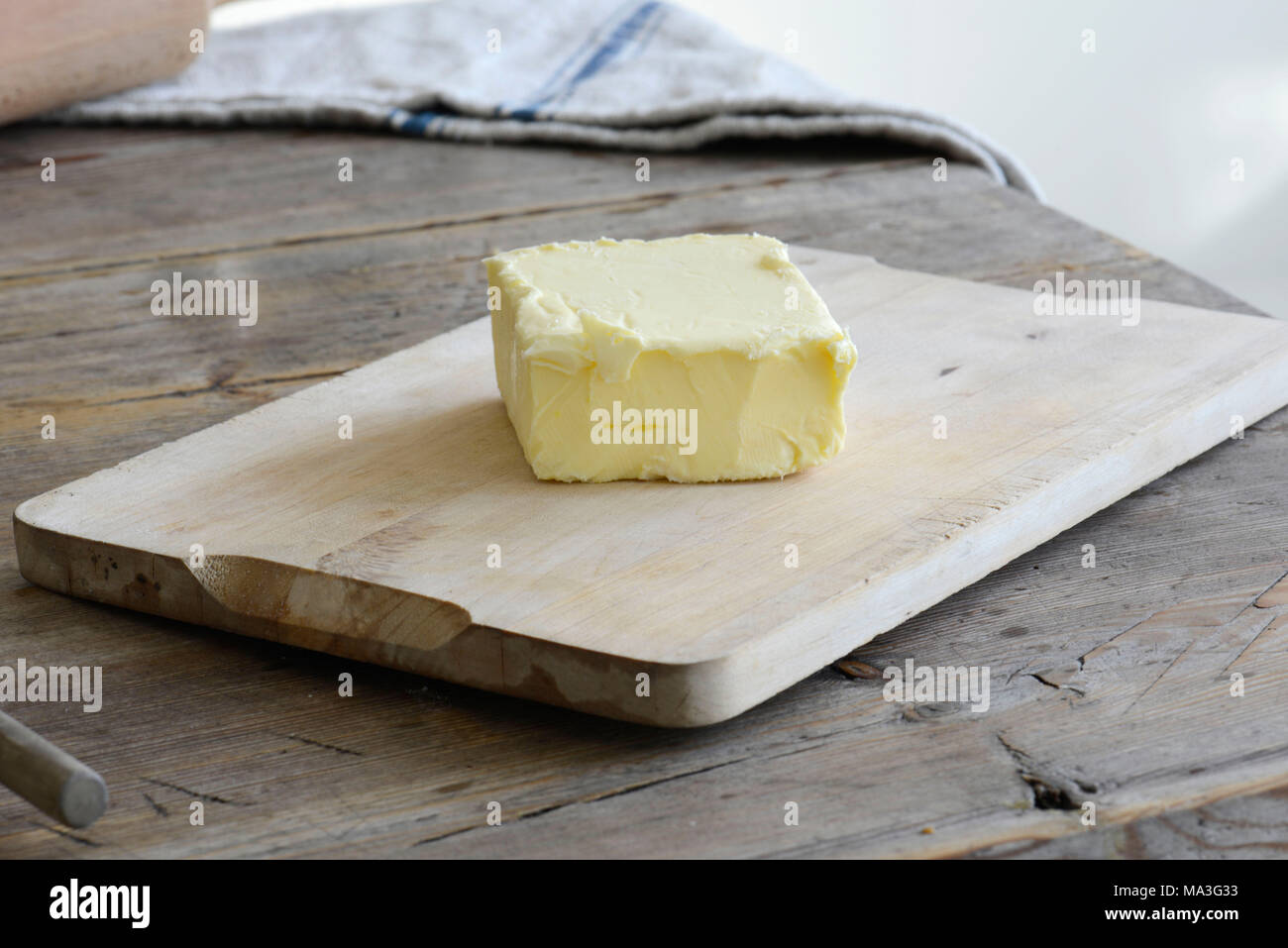 Butter, wooden board, wooden table - Stock Image