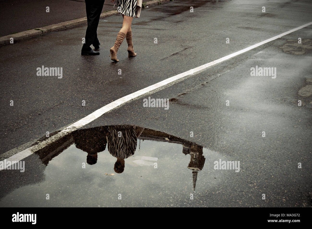 Reflection of a couple in a puddle afer rain, Helsinki, Finland Stock Photo