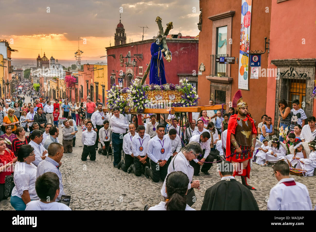 Catholic devotees kneel in prayer during the Las Cruzes del Señor Golpe procession through the streets at sunset as part of Holy Week March 28, 2018 in San Miguel de Allende, Mexico. The event is recreation of the passion of Jesus Christ on his way to Calvary for crucifixion. - Stock Image