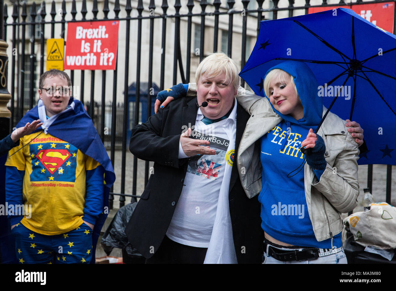 London, UK. 29th March, 2018. Pro-EU activists including Boris Johnson lookalike Drew Galdron and EU Supergirl and Young European of the Year 2018 Madeleina Kay protest opposite Downing Street to mark the first anniversary of the triggering of Article 50 and a year before the UK's exit from the European Union, or Brexit, is scheduled to take place. Protesters dressed as 'EU super heroes' and 'Brexit villains'. Credit: Mark Kerrison/Alamy Live News - Stock Image