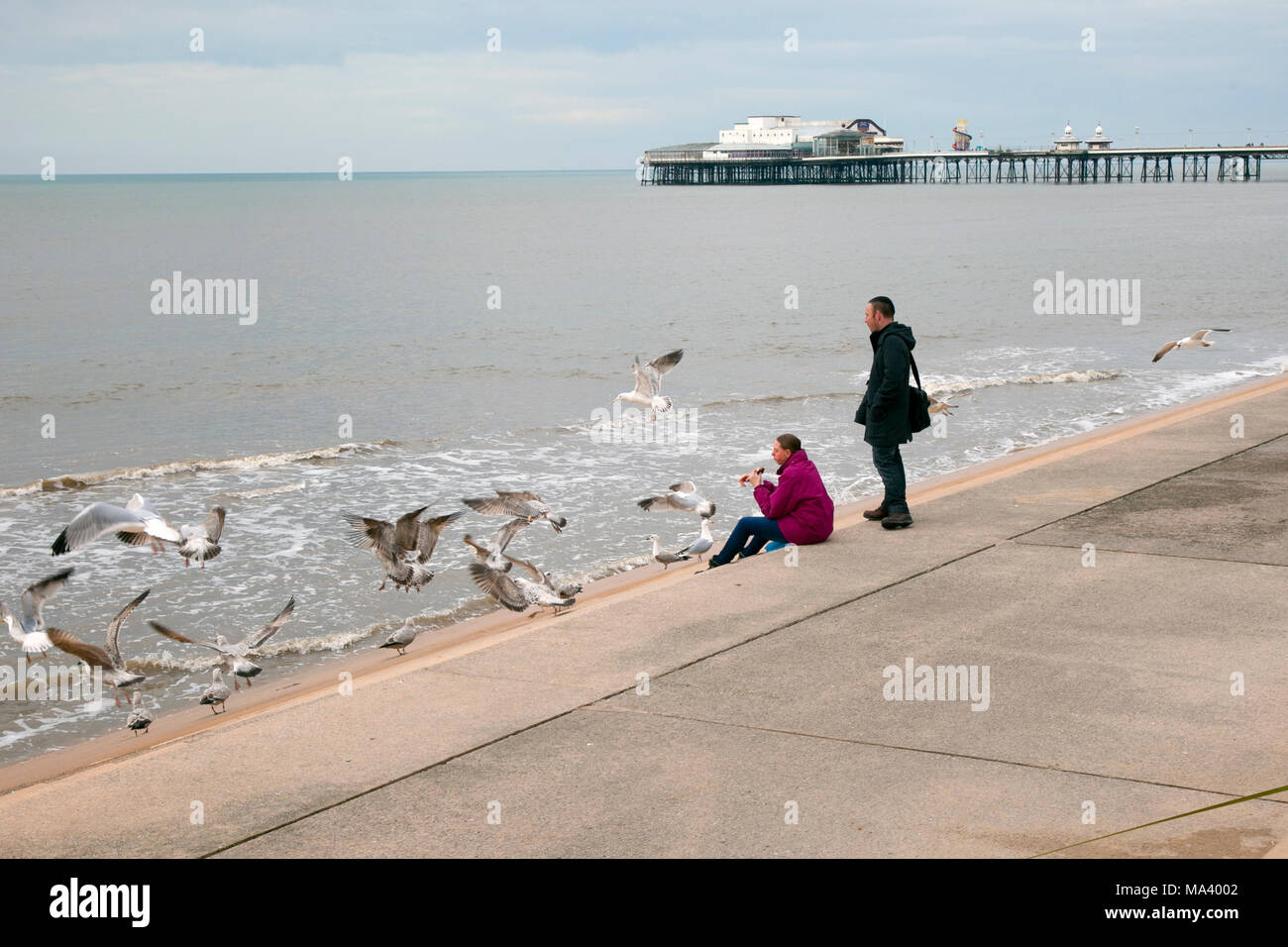 Holidaymakers on the seafront promenade at Blackpool, Lancashire. UK. 30th March, 2018   UK Weather.  Grey overcast day at the coast as visitors and holidaymakers arrive for the Easter Weekend.  Credit: MediaWorldImagesAlamyLiveNews. - Stock Image