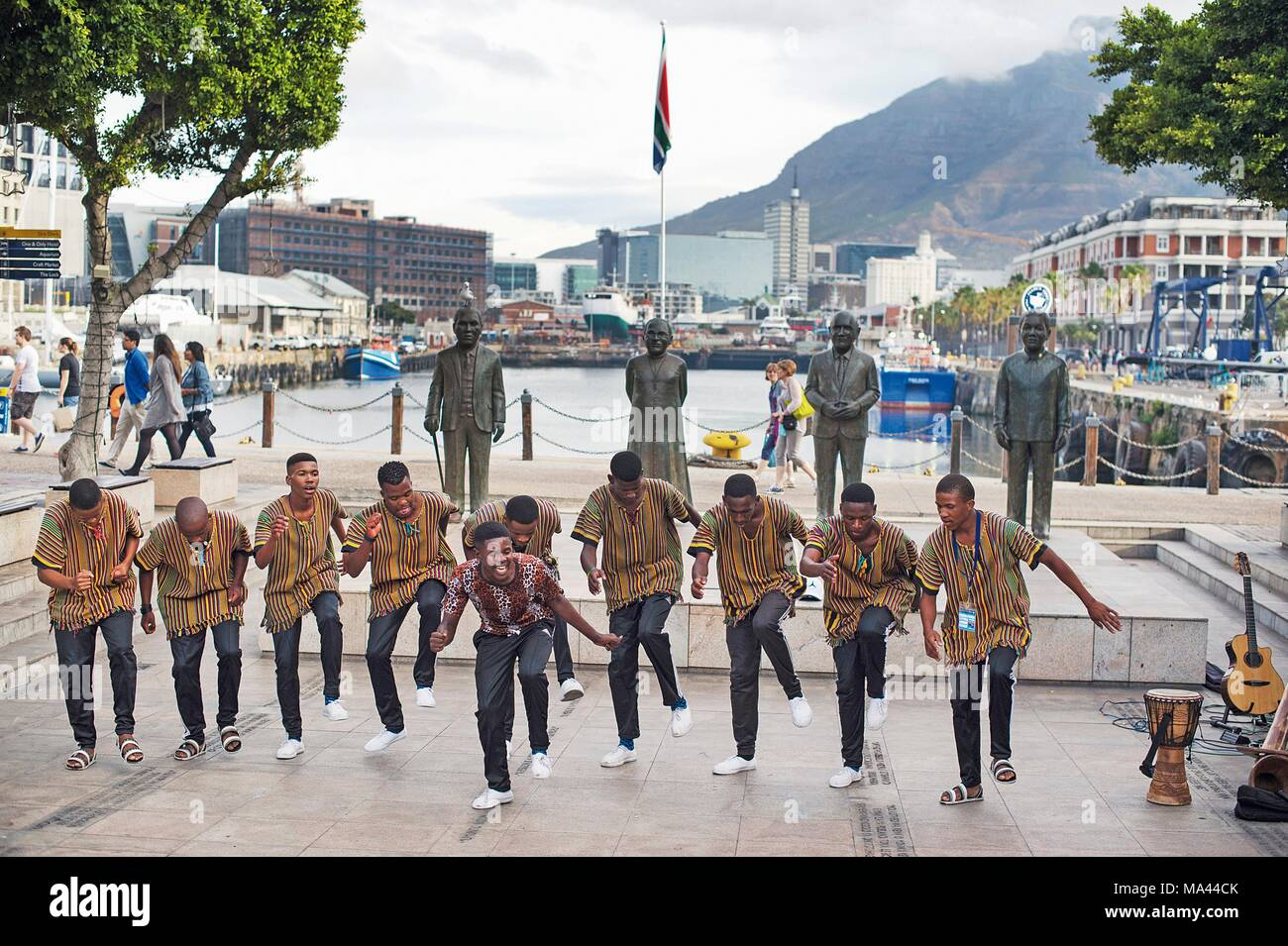 Dancers in front of the four bronze sculptures of the Nobel Peace Prize Laureates in Cape Town, South Africa - Stock Image