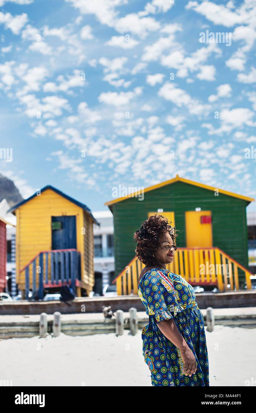 An African woman standing in front of the beach huts of Muizenberg in Cape Town, South Africa - Stock Image