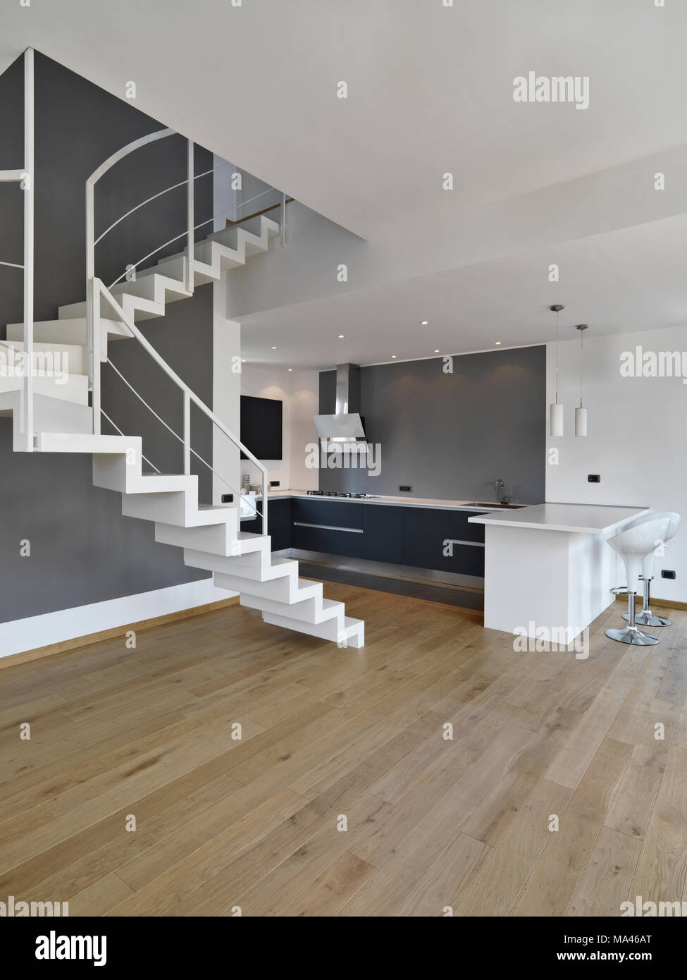 interiors shots of a modern kitchen with staircase and wooden flooting the walls are white - Stock Image