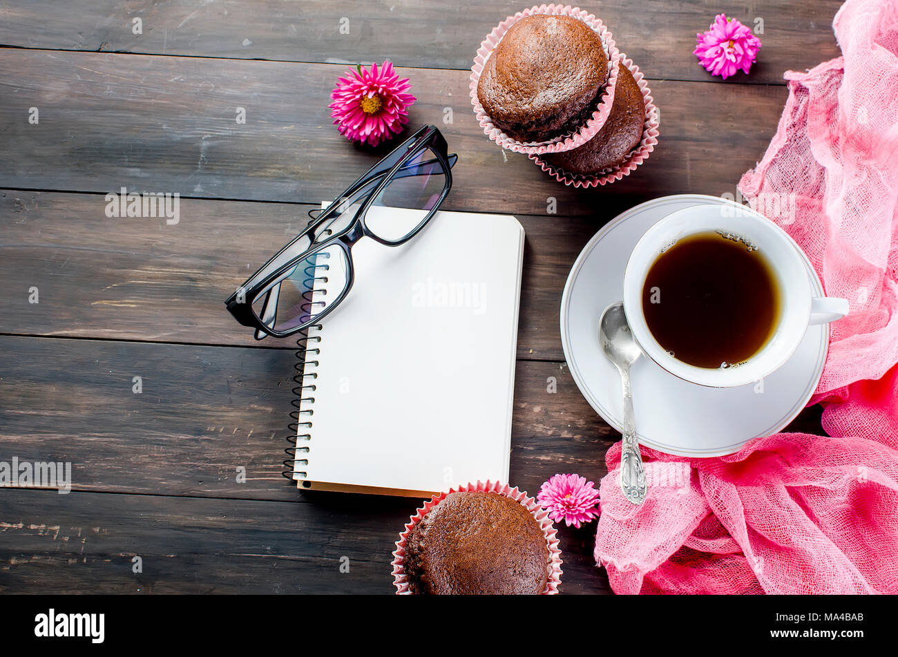 chocolate muffins and a cup of coffee breakfast and planning a day of a notebook, still life on a dark wooden table. Copy space, top view. - Stock Image