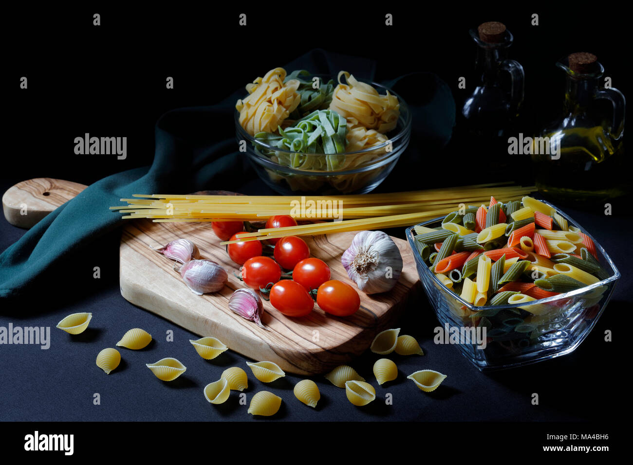 Chiaroscuro Dark Food Pasta ingredients with spaghetti,  tagliatelle and penne tricolore and garlic with olive oil with copy space - Stock Image