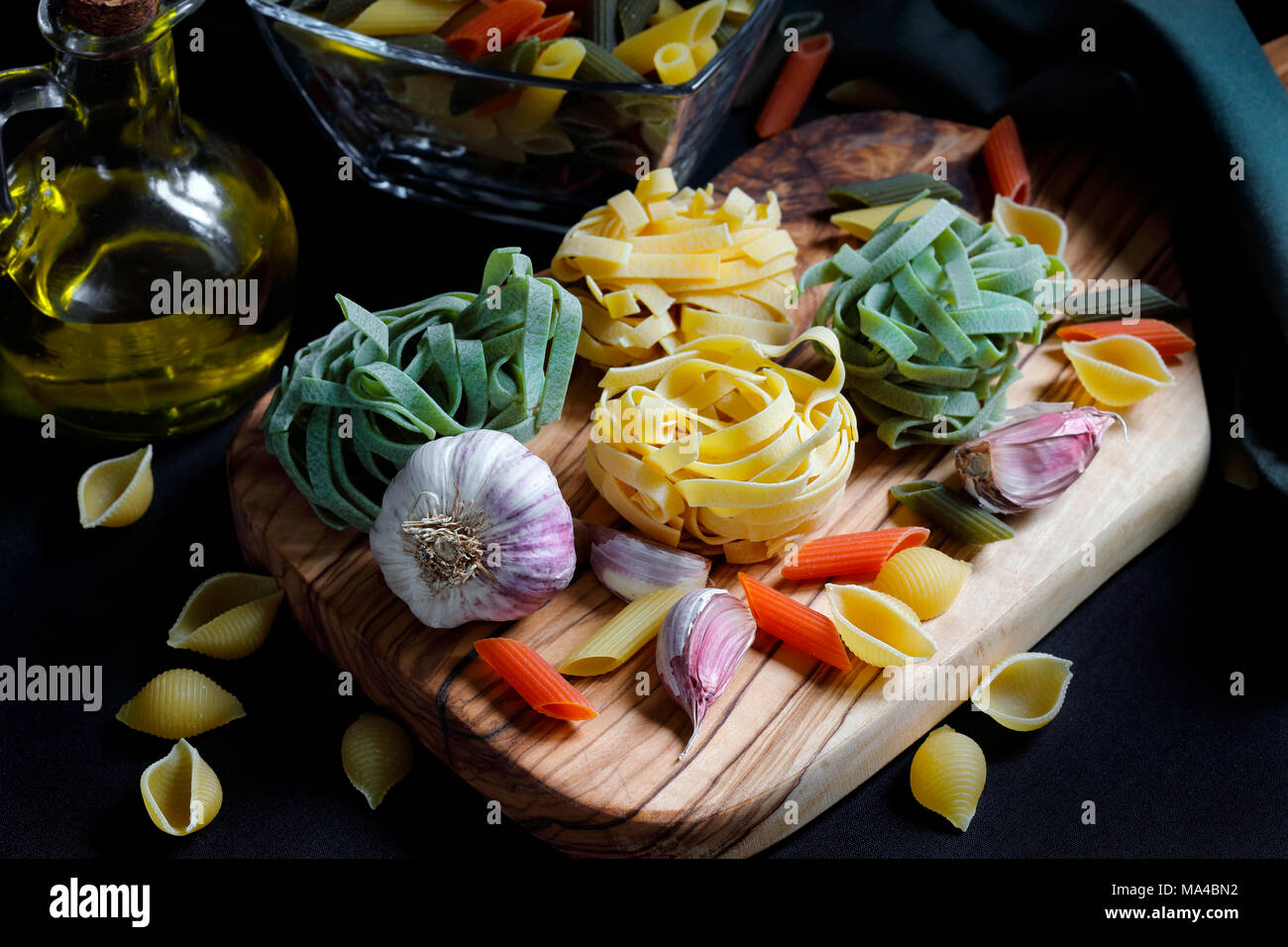 Close up Chiaroscuro Dark Food Pasta ingredients with spaghetti,  tagliatelle and penne tricolore and garlic and olive oil - Stock Image