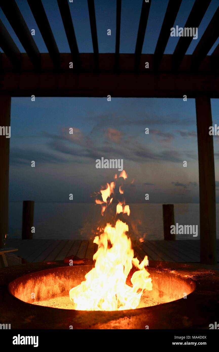 Flickering flames in outdoor fire pit along pier in Florida Keys, USA Stock Photo