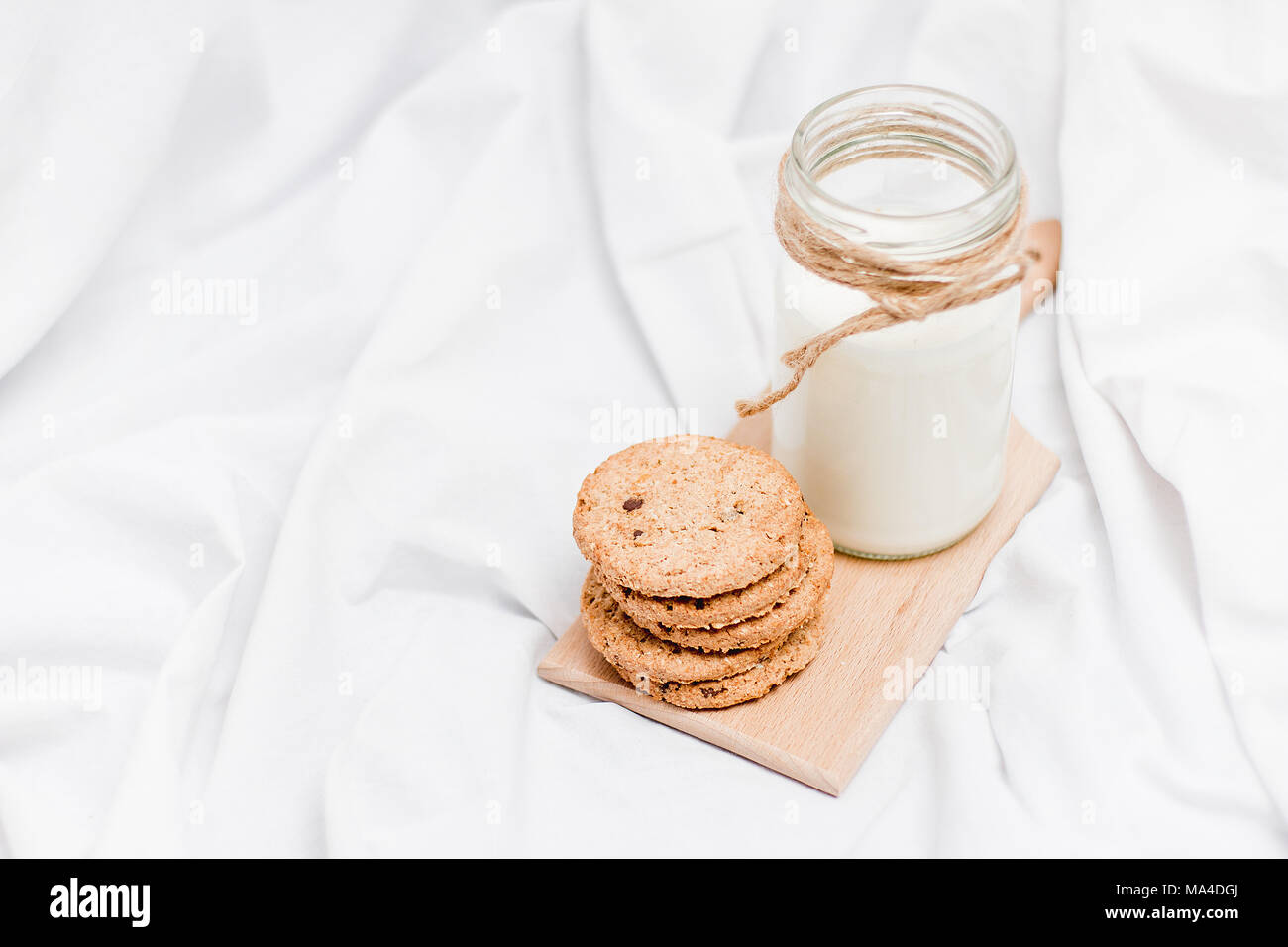 Photo of a jar of milk and cookies on a wooden board on a bed sheet - Stock Image