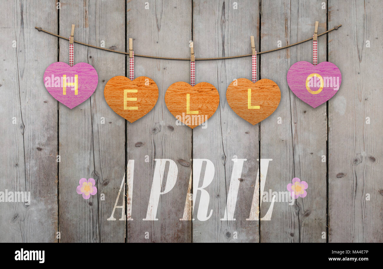 Hello April written on hanging pink and orange hearts and weathered wooden background, with flowers Stock Photo