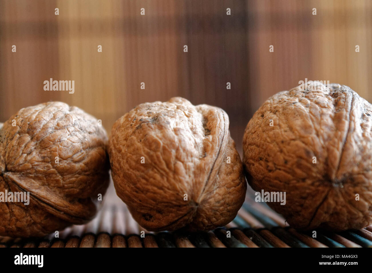 Three walnuts lie on a wooden bamboo table, background for web site or mobile devices. - Stock Image