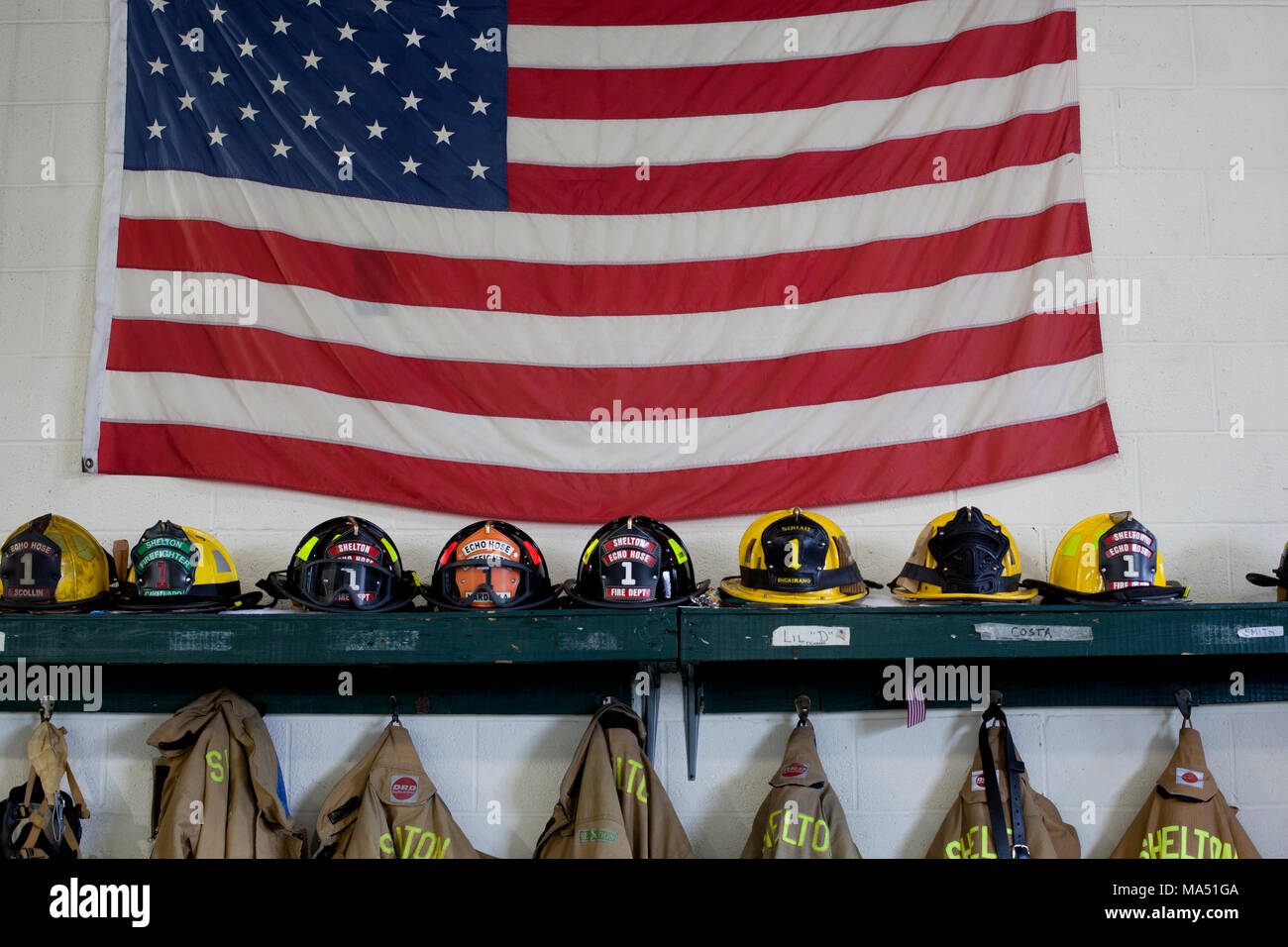 Protective gear, firemen's helmets, and turnout coats along with an American flag on display in the local volunteer firehouse - Stock Image