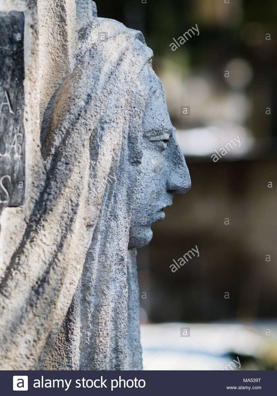Ancient slightly faided statue of a woman in a cemetry - Stock Image