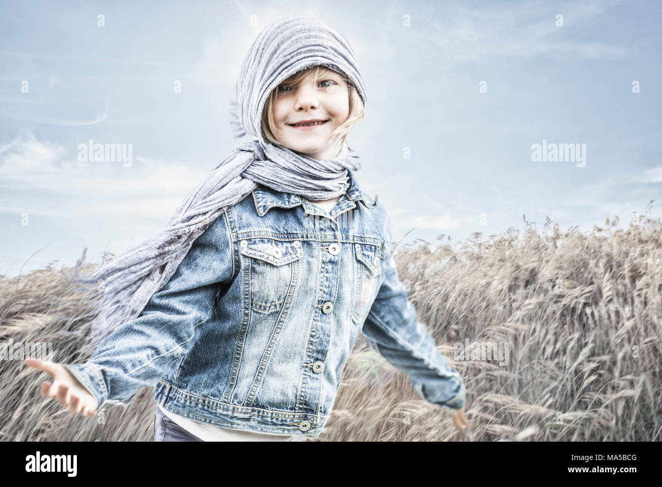 Little girl standing in a cornfield, against the wind Stock Photo