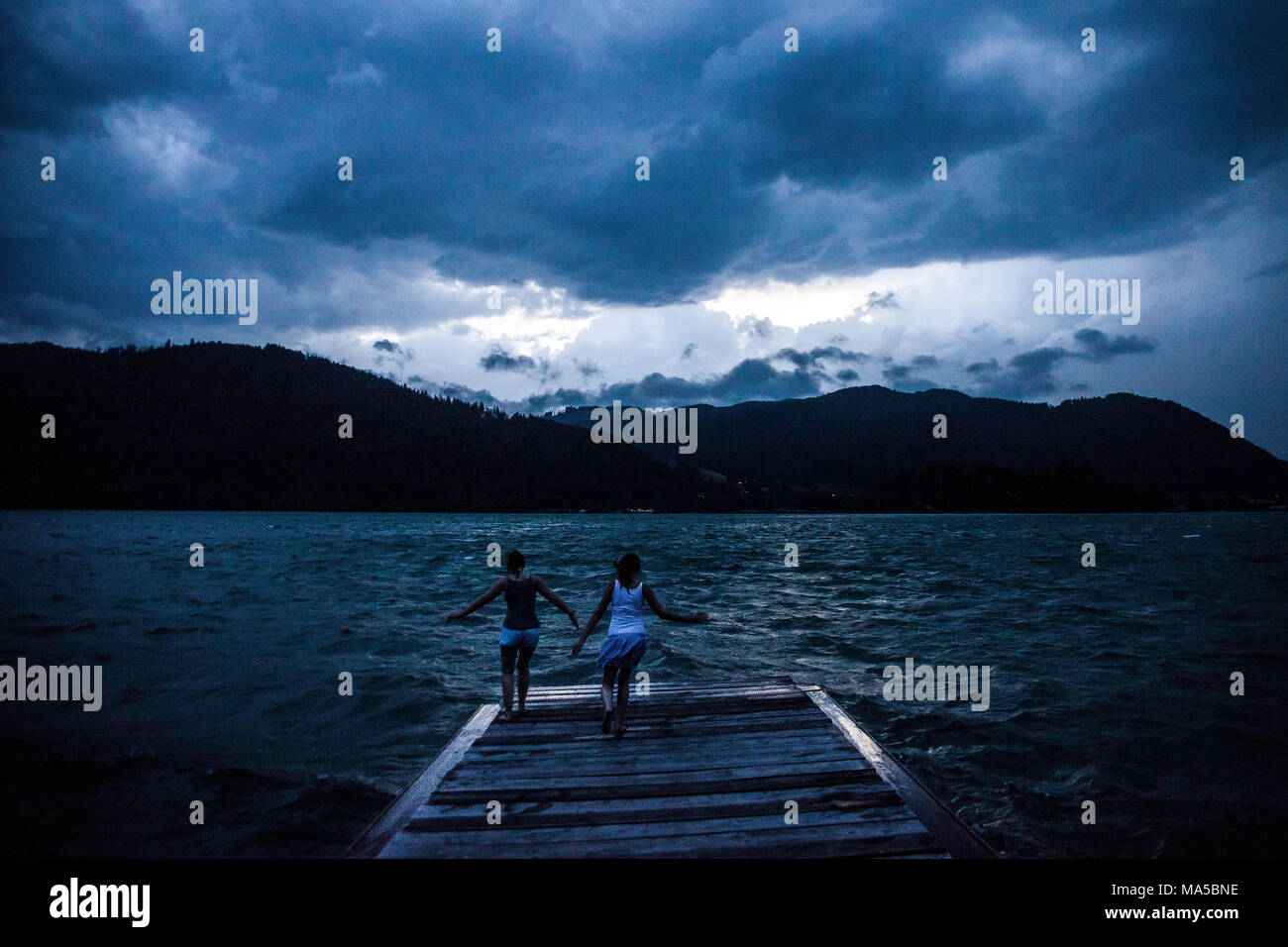 Two girls jump on a jetty on the Schliersee (lake) in expectation of a heavy thunderstorm - Stock Image
