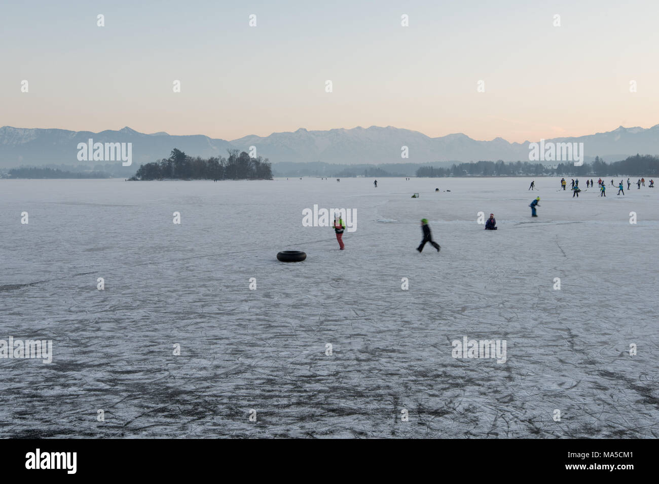 Children play on the frozen Staffelsee, ice hockey is played in the background - Stock Image