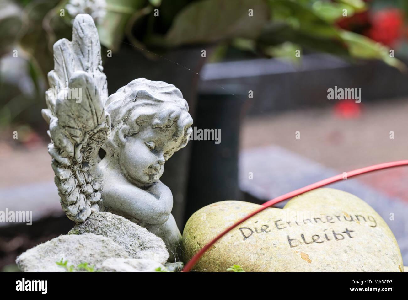 Angel figure, heart with ininscriptionion, 'Die Erinnerung bleibt', Friedhof Friedenstraße (cemetery), Wilhelmshaven, - Stock Image