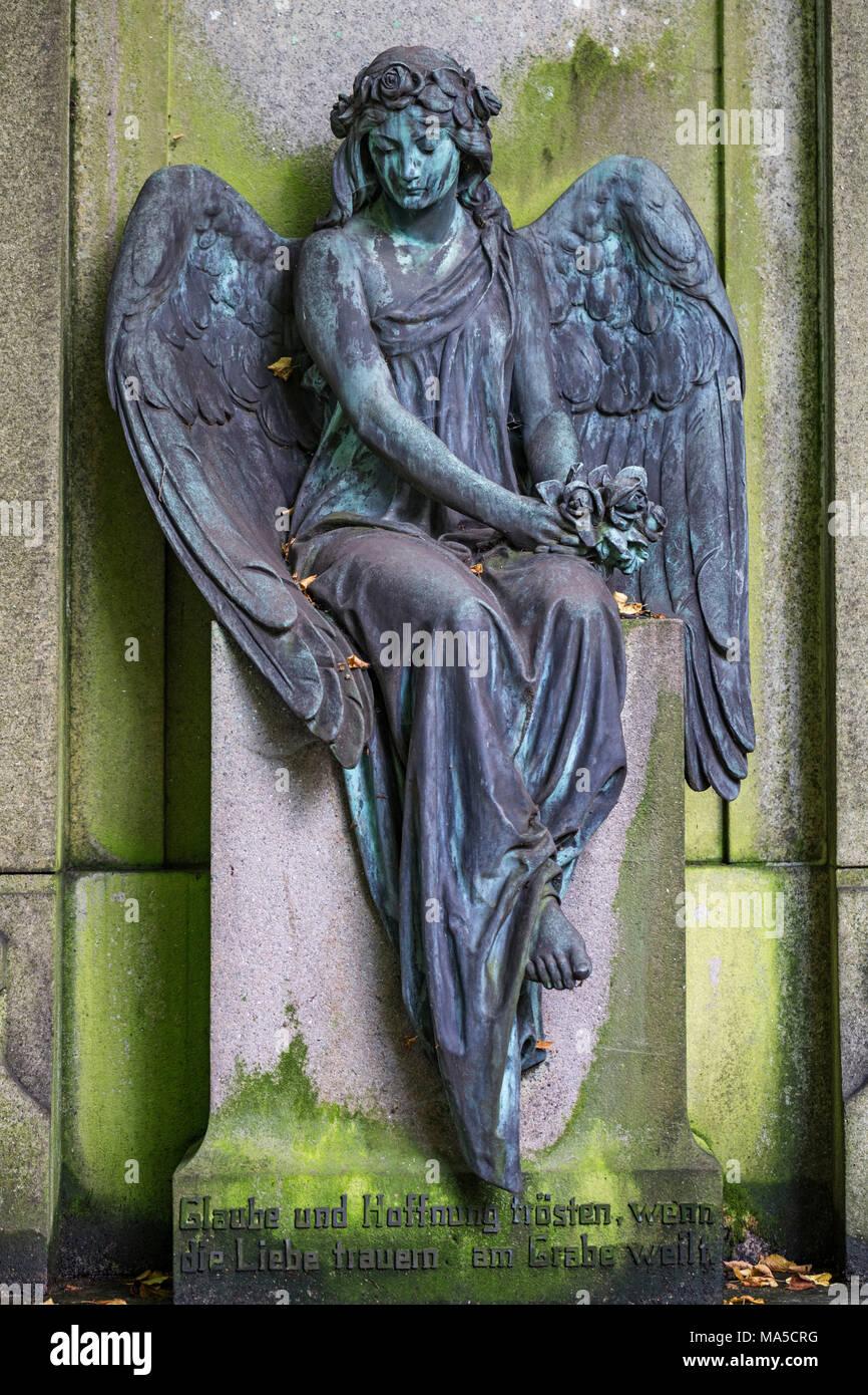 Angel statue, sitting, ininscriptionion, 'Glaube und Hoffnung trösten, wenn die Liebe trauern am Grabe weilt', Ohlsdorfer Friedhof (cemetery), Hamburg, - Stock Image