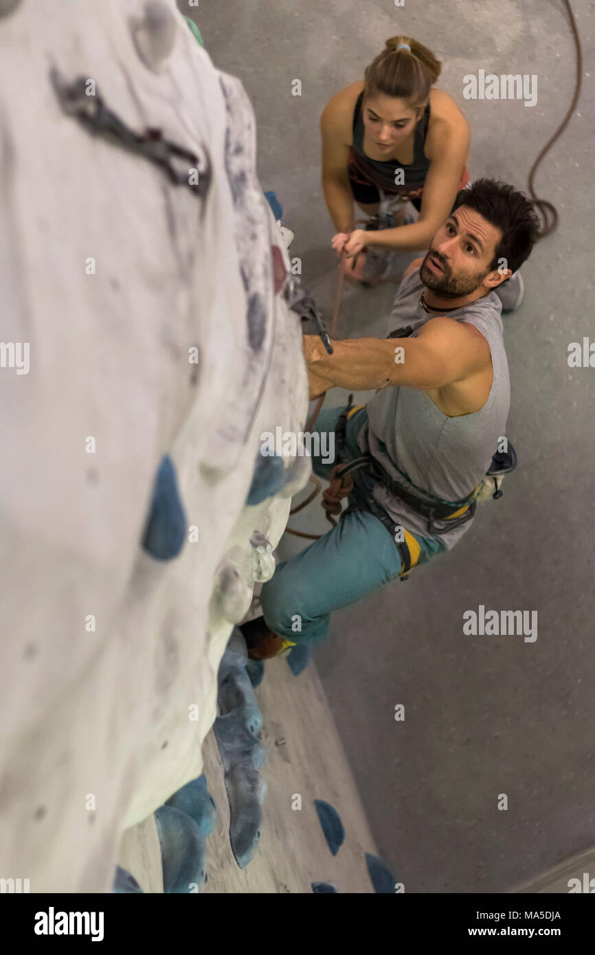 Germany, Baden-Württemberg, Stuttgart, climbing gym, climbing trainer in the lead secured by young climber - Stock Image