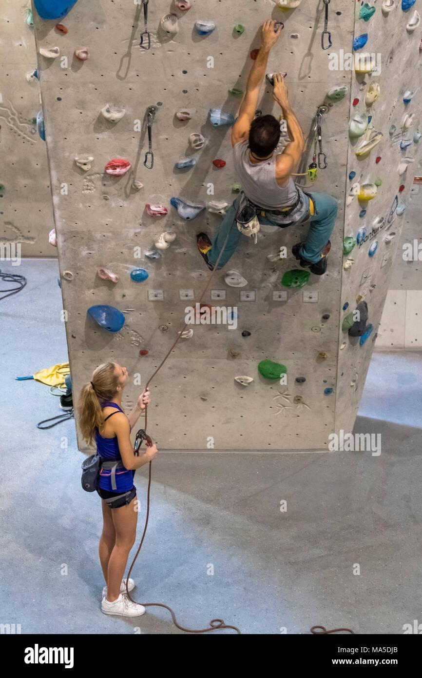 Germany, Baden-Württemberg, Stuttgart, climbing gym, climber belay climber on the climbing wall - Stock Image