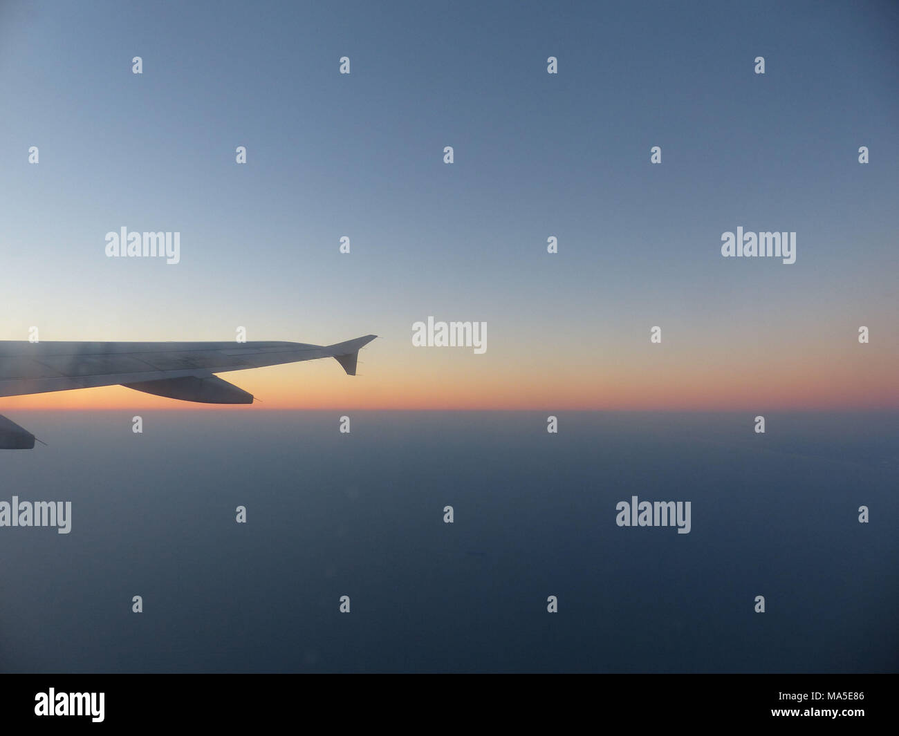 Wing of A 380 Airbus with sky illuminated by rising sun - Stock Image