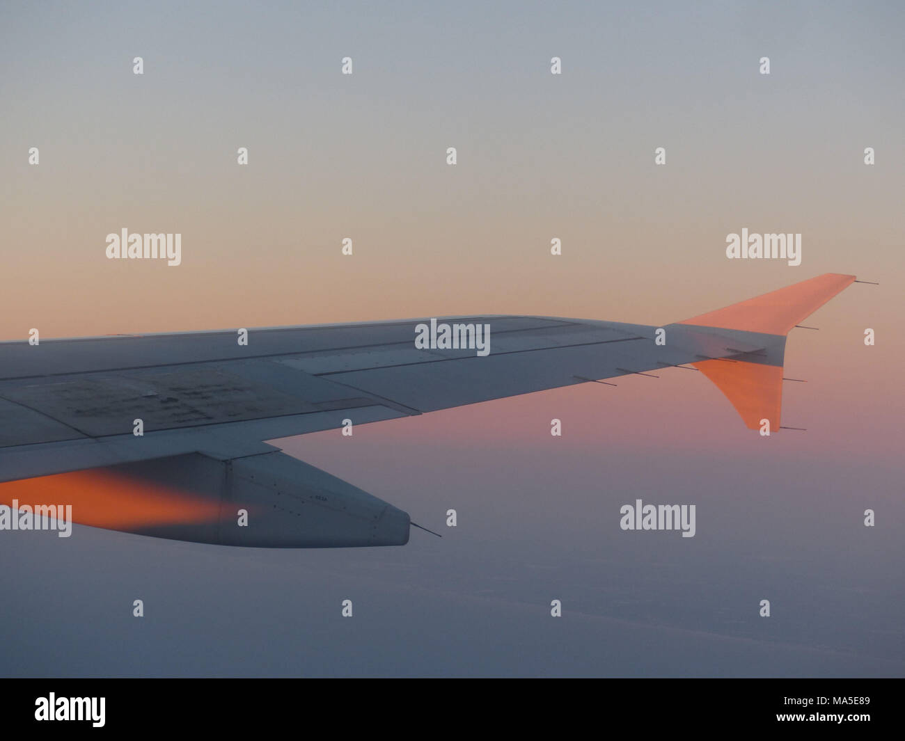 Wing of A 380 Airbus illuminated by rising sun - Stock Image