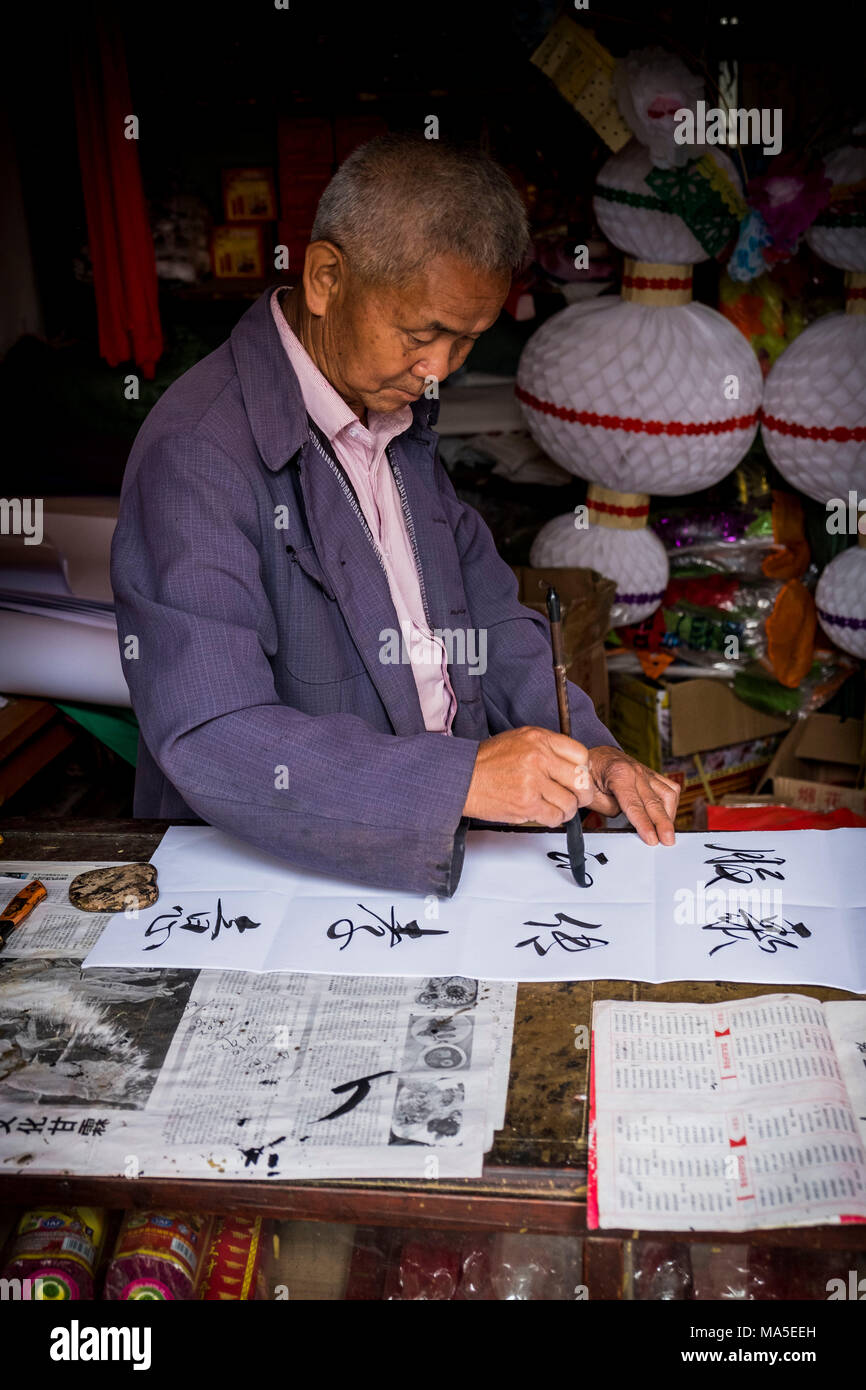Man is writing with chinese idioms at  Shigu Village or Stone Drum Village, Lijiang, Yunnan Province, China, Asia, Asian, East Asia, Far East - Stock Image