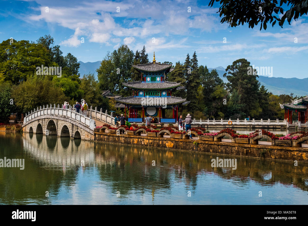 Tourists over arched bridge at Black Dragon Pool, Lijiang, Yunnan Province, China, Asia, Asian, East Asia, Far East - Stock Image