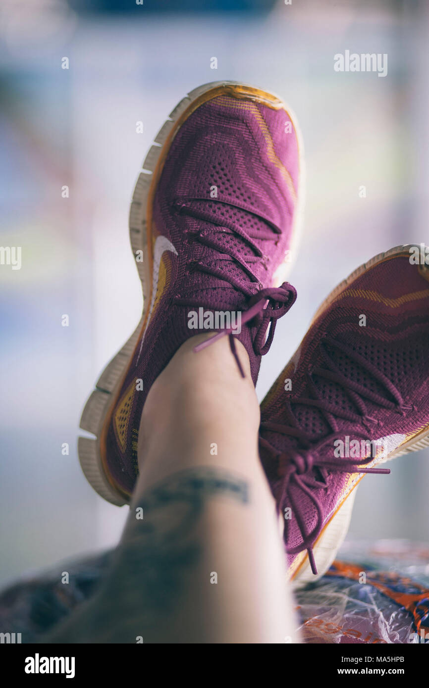 premium selection 8d521 6cee8 woman feet with sports nike tennis shoes waiting on an airport - Stock Image