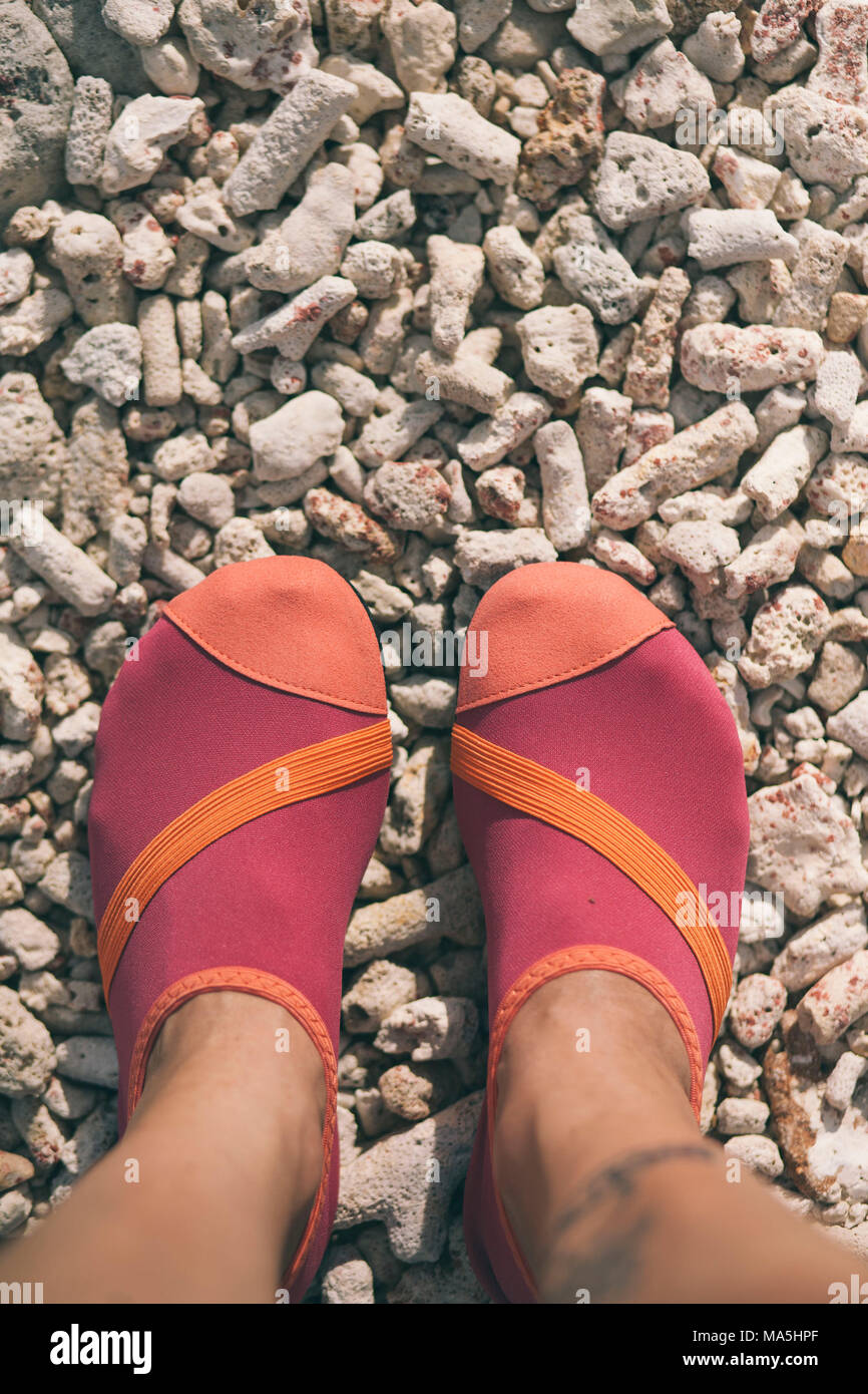 young woman legs in shorts with pink beach shoes stepping on the stones - Stock Image