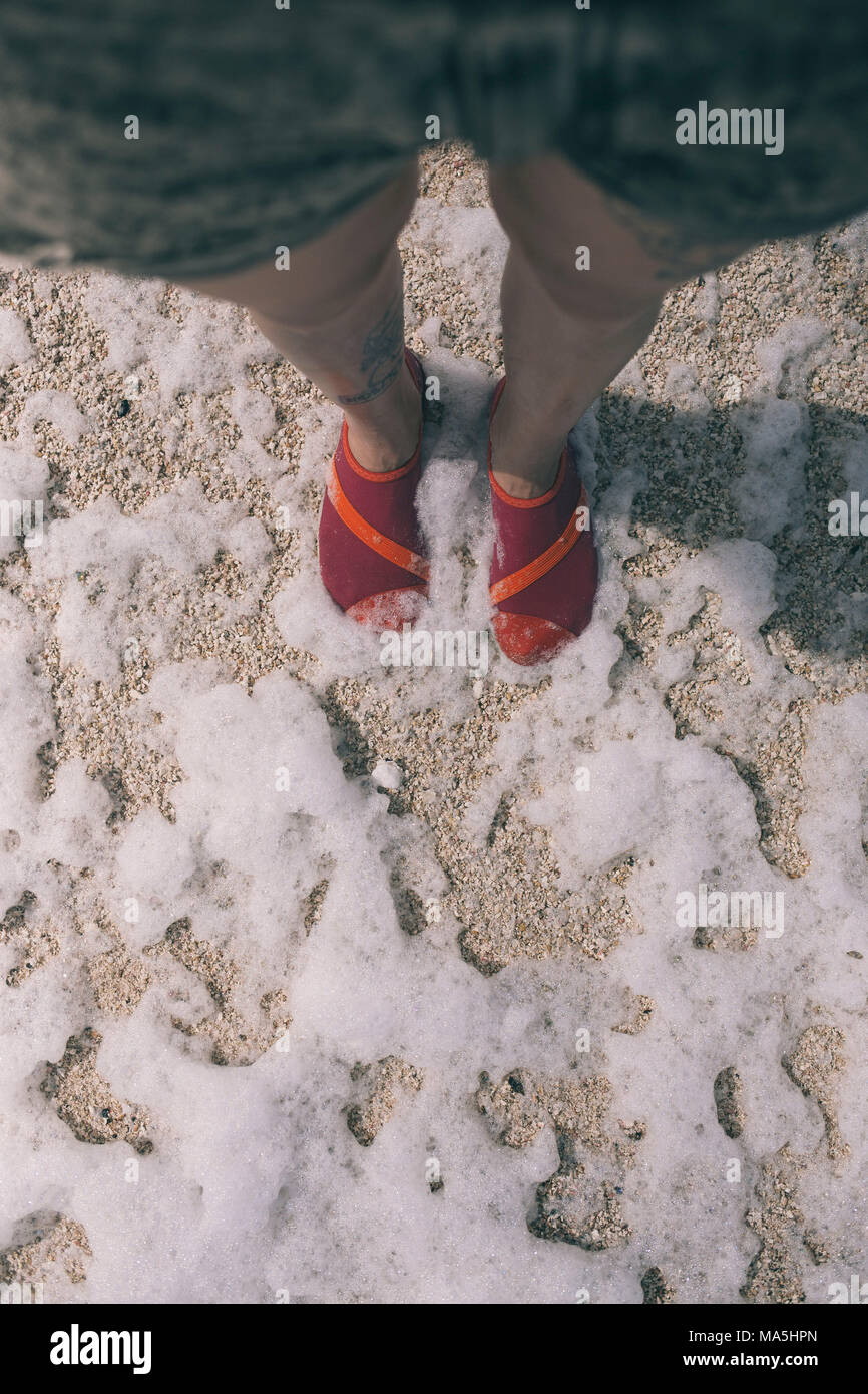 young woman legs in shorts with pink beach shoes stepping on the seafoam - Stock Image