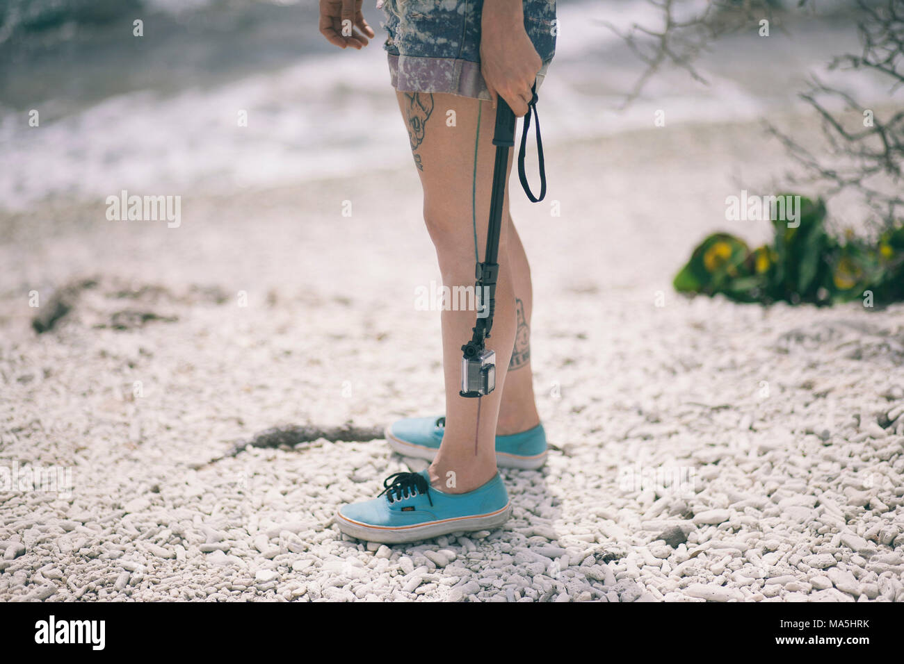 tourist tattooed girl hanging a subaquatic GoPro on the beach with shorts and tennis shoes - Stock Image